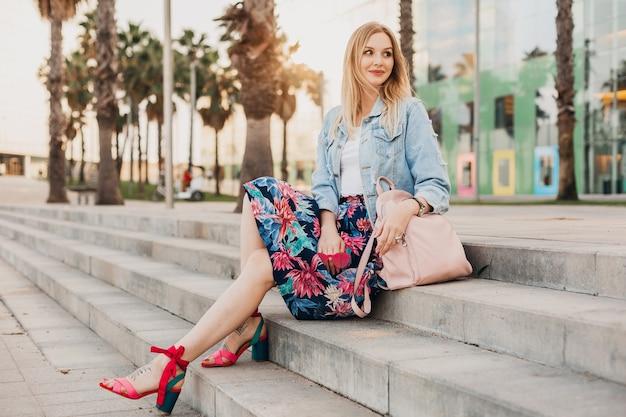Vrouw stijlvolle kleurrijke zomer outfit zitten in stad straat