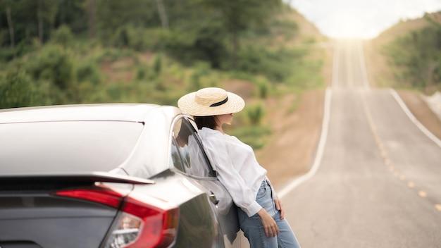 Vrouw stond met de auto. poseren met auto in mooie lege landelijke bocht, asfaltweg.