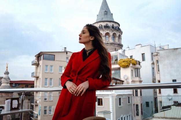 Vrouw stond op het dak café met istanbul op de achtergrond, uitzicht op de galata-toren in beyoglu, turkije. reizen en vakantie in turkije concept