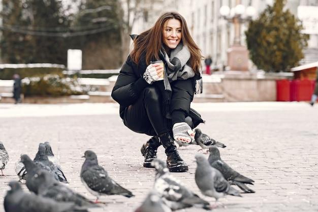 Vrouw stond op straat omringd door duiven