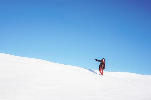 Vrouw stond op wit sneeuwveld overdag