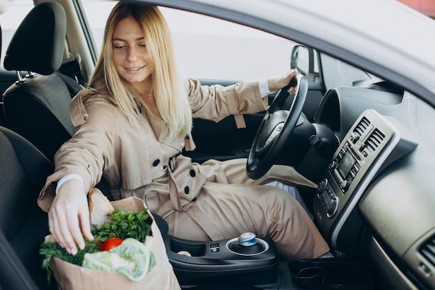 Vrouw stopt eten in boodschappentas in haar auto
