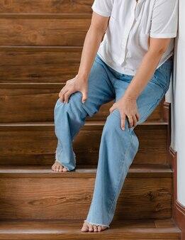 Vrouw stopt om uit te rusten en leunt tegen de muur voor steun terwijl ze met tintelende benen geen trappen kan lopen. concept van guillain-barre-syndroom en gevoelloze benenziekte of vaccin-bijwerking.