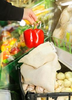 Vrouw stopt peper in herbruikbare boodschappentas. zero waste. ecologische en milieuvriendelijke pakketten. canvas en linnen stoffen. bewaar natuurconcept. geen plastic voor eenmalig gebruik in supermarkten.