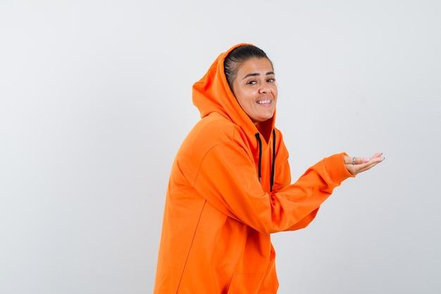 Vrouw strekt hand in oranje hoodie en ziet er behoeftig uit