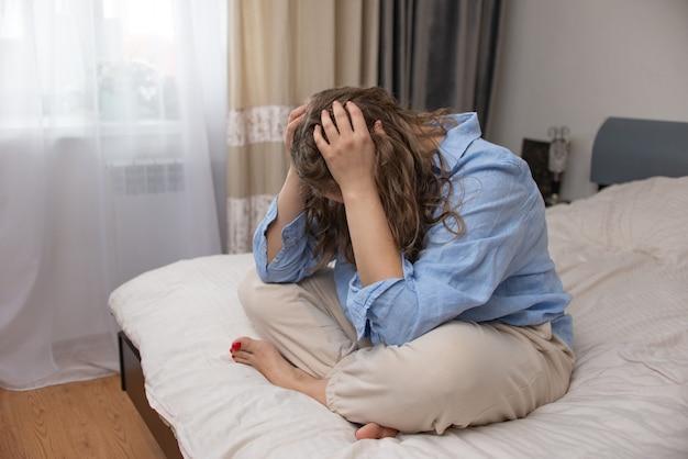 Vrouw stress alleen, verdrietig zittend op bed thuis in depressie. concept geestelijke gezondheid