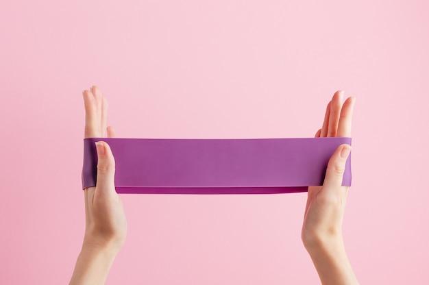 Vrouw stretch fitnessband. violet rubber voor thuisoefeningen.