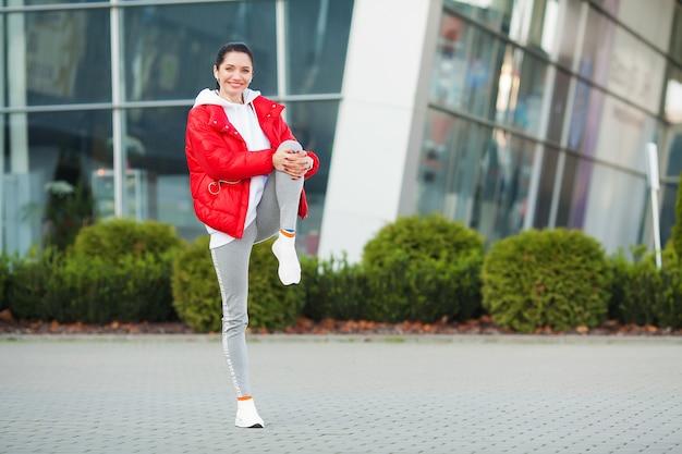 Vrouw stretching body, doen oefeningen op straat