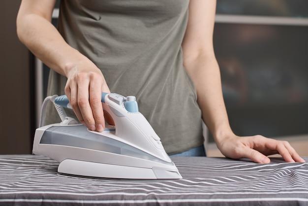 Vrouw strijken van kleding op strijkplank met modern strijkijzer
