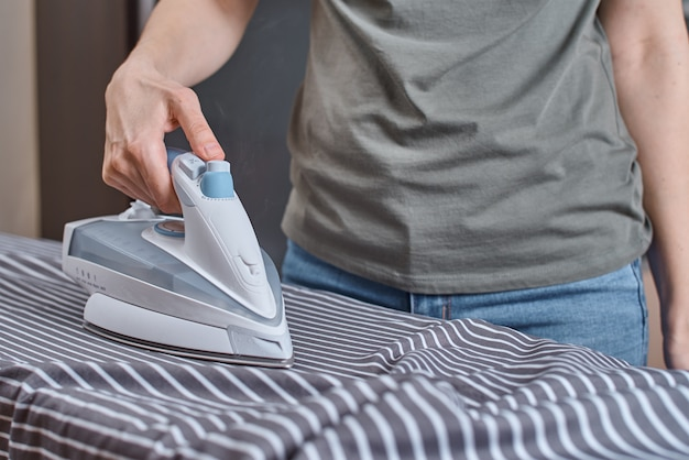 Vrouw strijken van kleding op strijkplank met moderne ijzer
