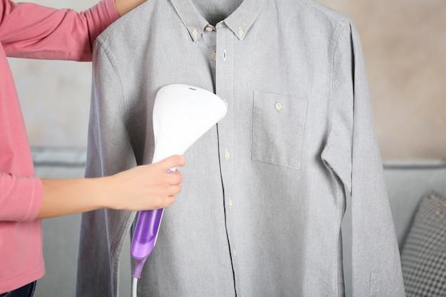 Vrouw strijkt hemd met kledingstomer