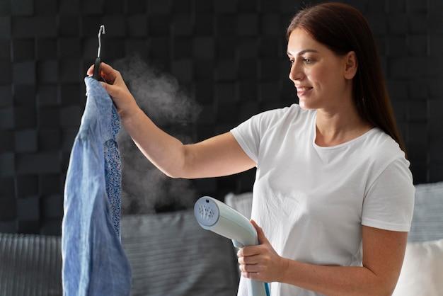 Vrouw strijkt het overhemd van haar man