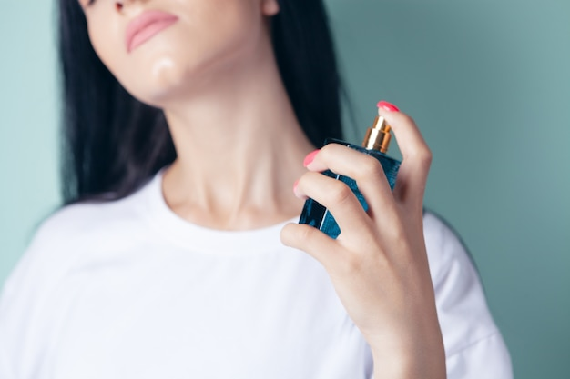Vrouw strooit parfum in haar nek