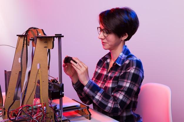 Vrouw student maakt het item op de 3d-printer