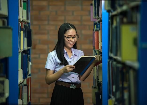 Vrouw studenten zijn een handvol boeken de boekenplank in de bibliotheek