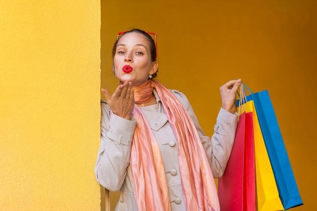 Vrouw stuurt kus voor je en houdt boodschappentassen vast
