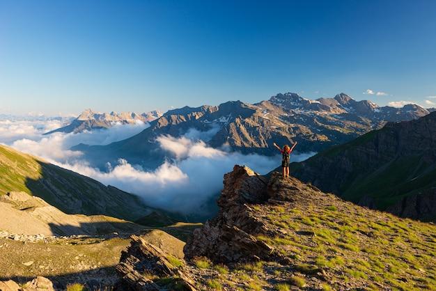Vrouw succes concept kijken naar uitzicht vanaf de bergtop, dramatische landschap wolken boven de vallei, zonsondergang helderblauwe hemel. zomeractiviteit fitness welzijn vrijheid eenzaamheid.
