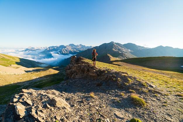 Vrouw succes concept kijken naar uitzicht vanaf de bergtop, dramatische landschap wolken boven de vallei,