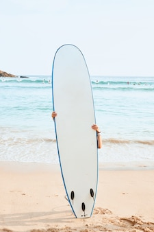 Vrouw surfer verbergen achter witte surfplank op strand