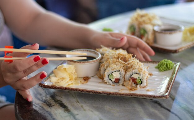 Vrouw sushi eten set met sojasaus, wasabi en stokken in restaurant