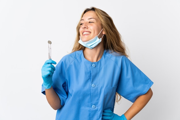 Vrouw tandarts houden tools geïsoleerd op een witte achtergrond poseren met armen op heup en glimlachen