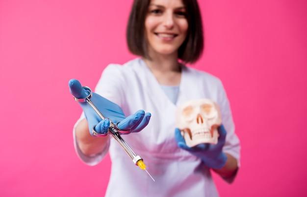 Vrouw tandarts met een carpoolspuit injecteert verdoving in het tandvlees van de kunstmatige schedel