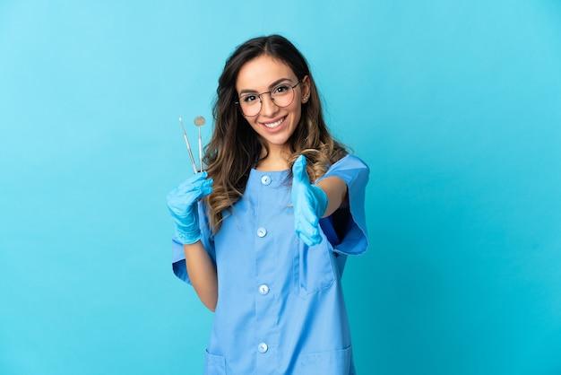 Vrouw tandarts met tools over geïsoleerd op blauwe ruimte handen schudden voor het sluiten van een goede deal