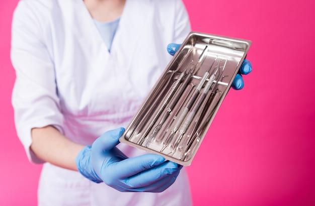 Vrouw tandarts opent een pakket steriele tandheelkundige instrumenten