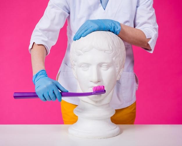 Vrouw tandarts tandenpoetsen van een antiek standbeeld met behulp van een grote tandenborstel