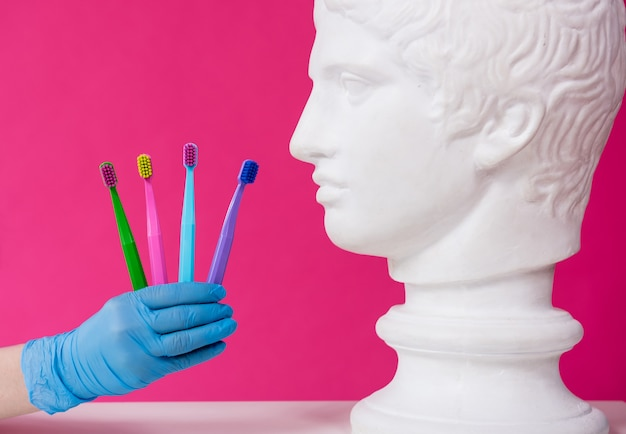 Vrouw tandarts tandenpoetsen van een antiek standbeeld met behulp van vier tandenborstels