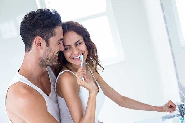 Vrouw tanden poetsen terwijl echtgenoot haar omhelst