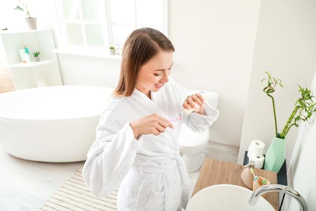 Vrouw tandenpoetsen in badkamer