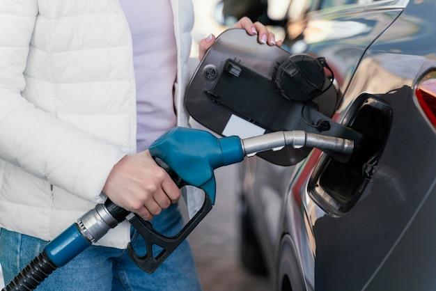 Vrouw tanken van de auto bij het benzinestation