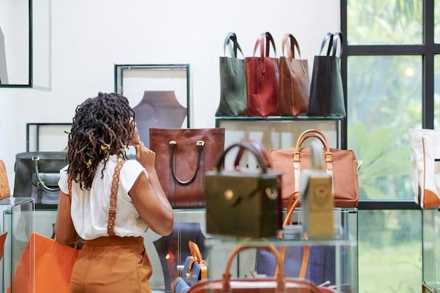 Vrouw tas in de winkel kopen