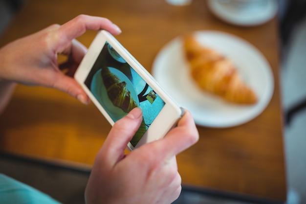 Vrouw te klikken foto van de croissant van een mobiele telefoon