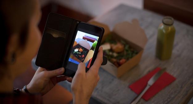 Vrouw te klikken op een foto van salade vanaf mobiele telefoon