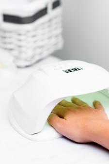 Vrouw te wachten met haar hand in de lamp voor haar manicure