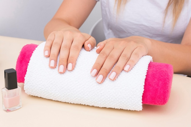 Vrouw te wachten om haar manicure te doen in de salon