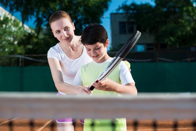Vrouw teachekid hoe te om tennis te spelen
