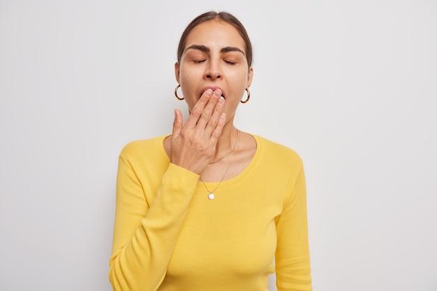 Vrouw tegen mond met hand houdt ogen gesloten draagt casual gele trui voelt vermoeidheid of slaperig staat op wit