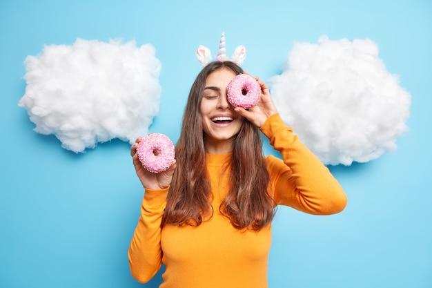 Vrouw tegen ogen met geglazuurde heerlijke donuts glimlacht positief heeft zoetekauw draagt oranje trui geïsoleerd op blauw