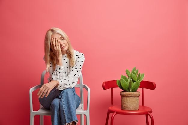 Vrouw tegens gezicht draagt stijlvolle polka dot blouse en jeans poses op comfortabele stoel met groene cactus geïsoleerd op roze