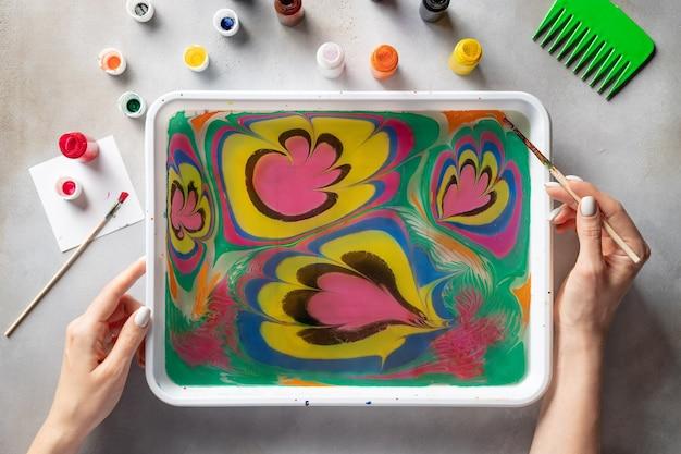 Vrouw tekenen met verf bloemmotief op water. ebru kunst