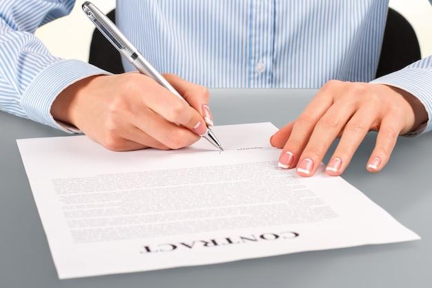Vrouw tekent contract aan balie. vrouw ondertekent contract aan balie. werkgever aan het bureau. recruiter op haar werkplek.