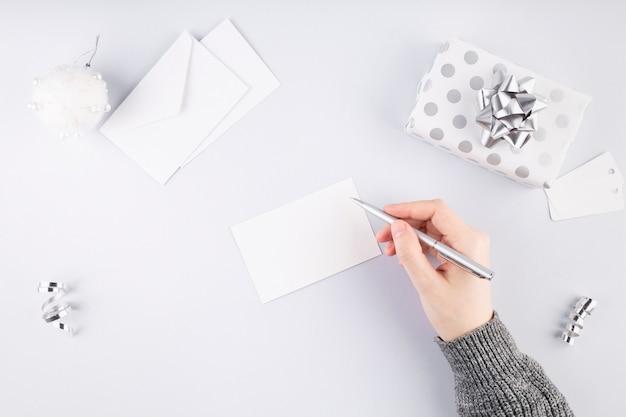 Vrouw tekent kaart voor cadeau in zilveren verpakking. concept voorbereiding op vakantie. bovenaanzicht. kopieer ruimte