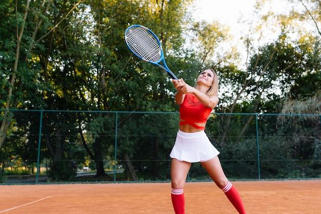 Vrouw tennissen bij de rechtbank en racket te houden