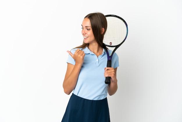 Vrouw tennissen geïsoleerde witte muur wijzend naar de zijkant om een product te presenteren