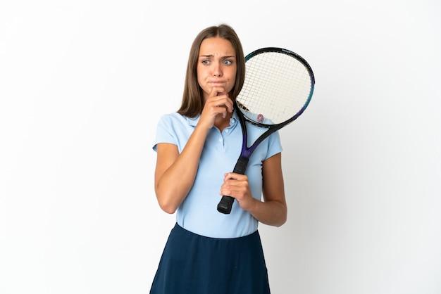Vrouw tennissen over geïsoleerde witte muur met twijfels en denken