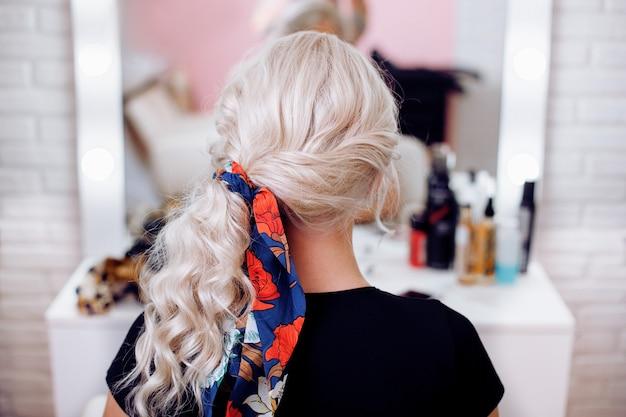 Vrouw terug met blond krullend haarstijl