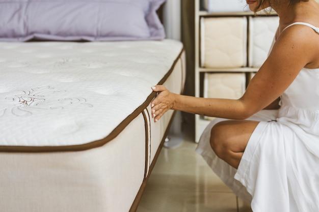 Vrouw testen matras in meubelwinkel